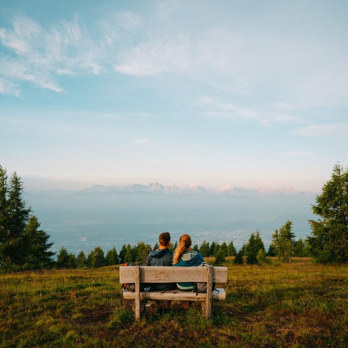 Ein Paar genießt beim Wandern in Villach Umgebung den Ausblick vom Berg