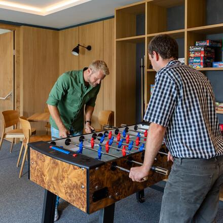 Zwei Männer spielen Tischfußball im 4-Sterne Hotel eduCARE in Treffen am Ossiacher See