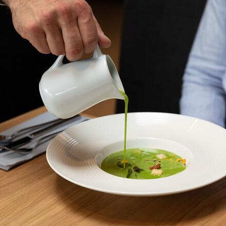 Ein Kellner serviert einem Gast das Essen im Hotel eduCARE in Treffen am Ossiacher See