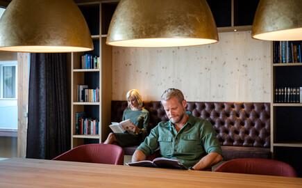 Ein Pärchen liest im Freizeitraum vom Hotel eduCARE