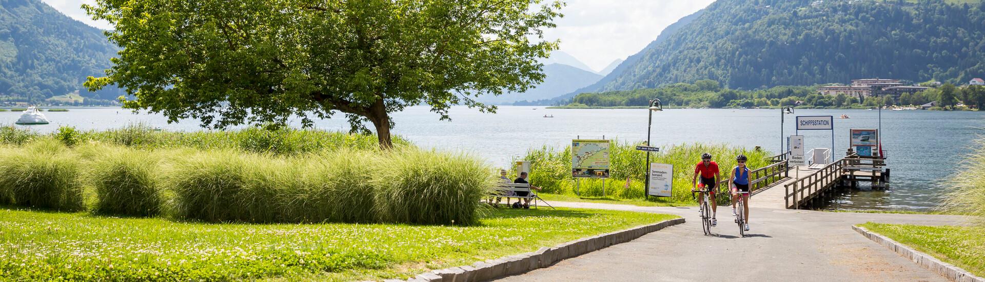 Ein Paar fährt beim Radurlaub in Kärnten am Seeufer entlang