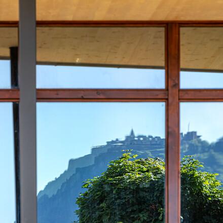 Die Reflexion der Burg Landskron im Fenster vom Hotel eduCARE am Ossiacher See