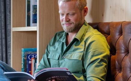 Ein Mann liest gemütlich eine Zeitschrift im Freizeitraum vom 4-Sterne Hotel eduCARE am Ossiacher See