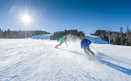 Ein Skifahrer und ein Snowboarder sausen beim Urlaub am Ossiacher See die Piste hinunter